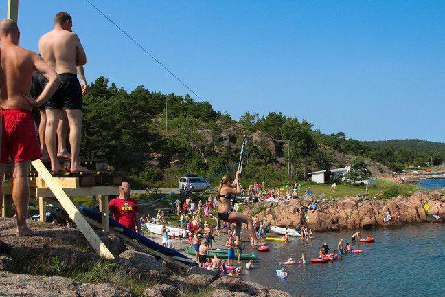 Barn og voksne som leker ved vannet