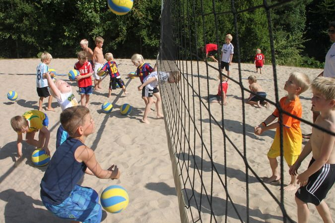 Barn som leker med volleyballer på en volleyballbane